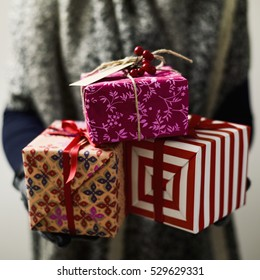 Closeup Of A Young Caucasian Woman Holding Pile Cozy Christmas Gifts In Her Hands