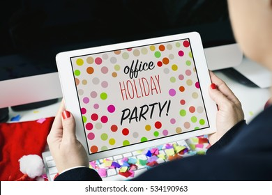 closeup of a young caucasian woman sitting at her office desk full of confetti looking to her tablet, with the text office holiday party in its screen