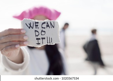 closeup of a young caucasian woman in the street showing a piece of paper with the text we can do it written in it