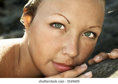 Close-up of young Caucasian woman's face with wet hair.