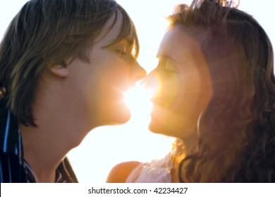 Close-up of a young couple kissing each other in the light of sunset