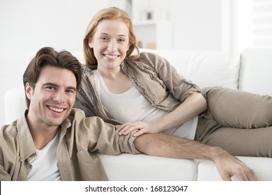 closeup of young couple in living room looking at camera
