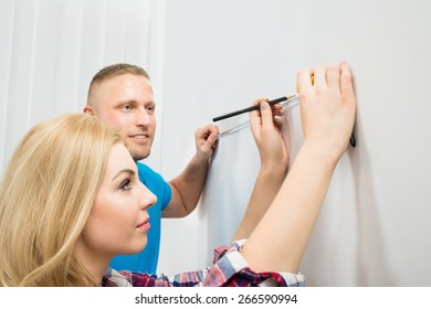 Close-up Of Young Couple Measuring Wall With Measurement Tape And Pencil