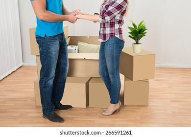 Close-up Of Young Couple In New Home Holding Hands