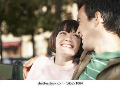 Closeup of a young couple smiling at each other on park bench