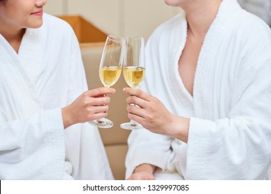 Close-up of young couple wearing white bathrobes holding glasses of champagne and toasting while sitting in wellness centre