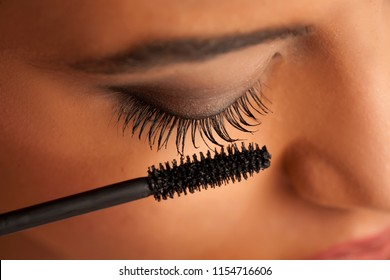 closeup of a young dark-skinned woman applying mascara on a white background