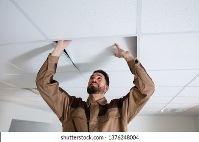 Close-up Of Young Electrician Repairing Ceiling In Office