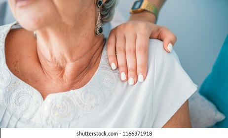 Close-up of young elegant woman's hand on senior lady's shoulder.  Sign of caring for seniors. Helping hands. Care for the elderly concept. Elderly woman having private medical care
