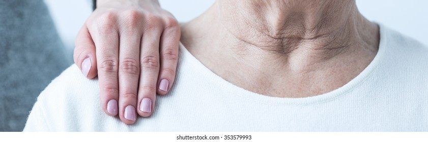 Close-up of young elegant woman's hand on senior lady's shoulder