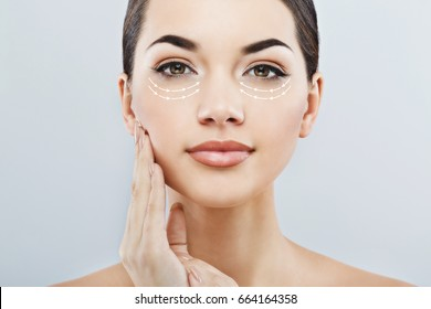 Closeup of young female with clean fresh skin, antiaging concept.  Beautiful girl with big eyes and dark eyebrows touching face and looking at camera,  lifting arrows under eyes