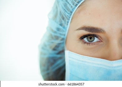 Close-up of young female doctor with a mask on face