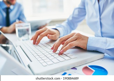 Close-up of young female hands pressing laptop buttons