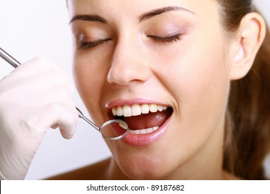 Close-up of young female having her teeth examinated isolated on white background