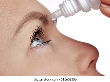 Close-up of young female using drops for tired and sick eyes. Concept of eye care, allergy treatment and medicine.