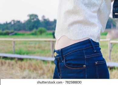 Closeup of young fit woman's belly outdoors , Pretty Girl show slim belly.