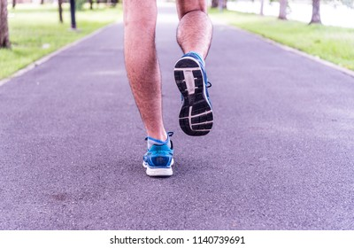 Closeup of young fitness man jogging outdoor on road - runner legs and running shoes