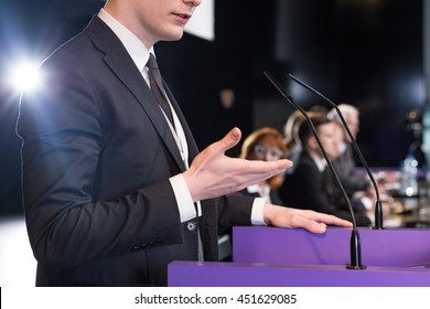 Close-up of a young formally-dressed man giving a public speech in a conference room