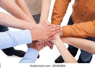 Closeup of young friends with their hands stacked together over white background