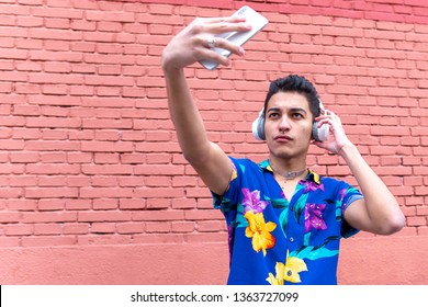 close-up of a young gay man with pierced nose, mobile phone making himself a selfie listening to music with his vintage helmets with a red brick wall background. concept of transgression and lifestyle