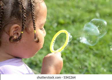 A close-up of a young girl blowing soap bubbles