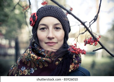 (Close-up  of young girl dressed in dark coat, knitted cap and shawl with flower pattern, standing under the branches with red rowan berries, looking straight to the camera; pale blurred background