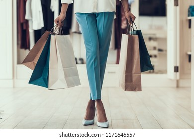 Closeup Young Girl holding Shopping Bags in Store. Close up of Black Girl holding Shopping Paper Bags in Boutique inside Mall. African Woman in Clothing Store. Woman shopping Concept