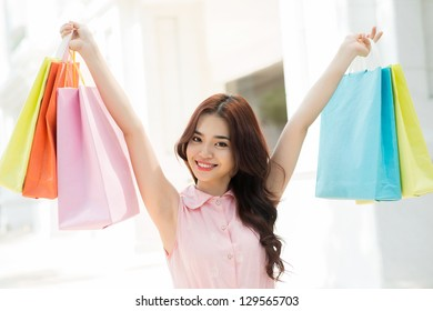 Closeup of a young girl holding shopping bags up