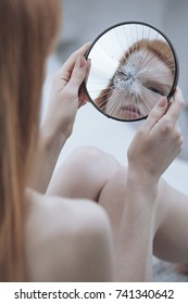 Close-up of young girl with mental problem feeling ugly and hate yourself while looking at mirror