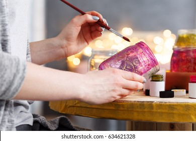 Close-up of young girl painting a pink jar