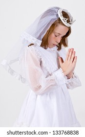A close-up of a young girl praying in her First Communion Dress and Veil