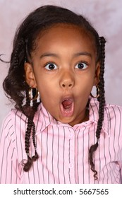 A close-up of a young girl pretending to be very surprised