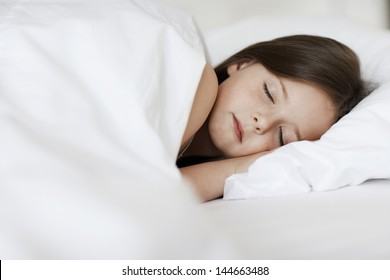 Closeup of young girl sleeping in bed cover with white blanket