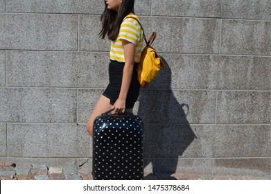 Closeup of young girl in yellow white stripe shirt and black jeans shorts walking next to grey stone wall. Carrying black suitcase with white polka dots and a yellow leather backpack. Travel concept.