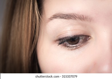 Closeup of young girl's brown eye looking down