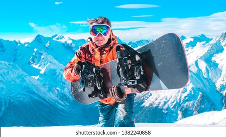 Close-up: A young guy in ski equipment is standing with a snowboard against the background of a panorama of a snowy mountain range. Young snowboarder high in the mountains