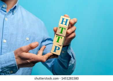 Close-up - young guy wearing blue shirt holding wooden cubes with HTTP letters.