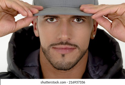 closeup of young handsome male model starring at camera and holding cap with both hands