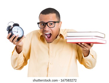Closeup of a young handsome man, wearing big glasses, holding books and clock, anxious in anticipation of finals test, isolated on white background. Negative facial expressions, feelings, emotion