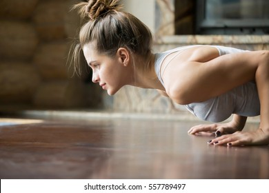 Closeup of young happy attractive woman practicing yoga, doing four limbed staff, push ups or press ups exercise, chaturanga dandasana pose, working out, wearing sportswear, bra, indoor, home interior