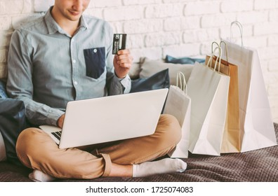 Closeup young happy man sit on couch, using laptop for safe online shopping from home. Stylish male hipster shopper hold credit card in hand. Payments and purchases at internet store. Man shopaholic