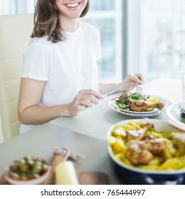 Close-up of young happy woman enjoying healthy dinner while sitting at the table on modern kitchen at home