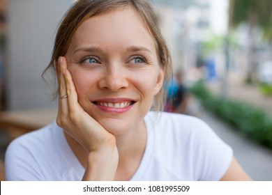 Close-up of young happy woman wearing white T-shirt looking away. Face of Caucasian girl looking away and smiling outdoors. Dream and happiness concept