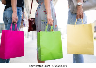 Closeup of young happy women with colorful shopping bags