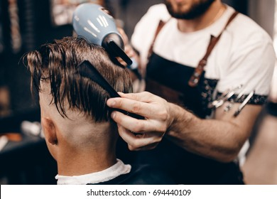 Close-up of young hipster guy in barber shop hairdresser cutting hair with scissors and typewriter, blow-drying. Concept men place, toned photo. Soft focus.