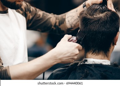Close-up of a young hipster guy in a barbershop hairdresser cutting hair with scissors and a typewriter, blow-drying. Concept men's place, toned photo. Soft focus.