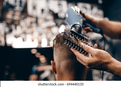 Close-up of a young hipster guy in barbershop hairdresser cutting hair with scissors and a typewriter, blow-drying. Concept men's place, toned photo. Soft focus.