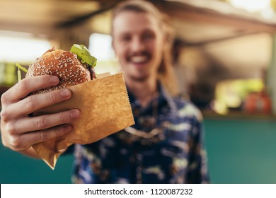 Closeup of young hipster man holding a burger in hands. Focus on hands holding food truck burger.