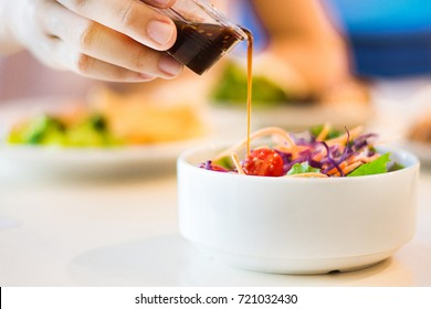 Close-up of young housewife dressing salad with sauce from bottle in kitchen.Fresh vegetable salad and dressing in Japanese style.Only hands.Housewife preparing salad.Focus on hand