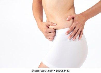 Closeup of a  young lady checking her fats against  white background